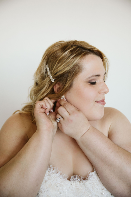 Milwaukee bride putting on earring at The Brewhouse Inn & Suites located in Milwaukee, WI