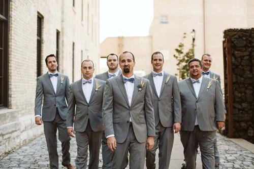 Groom and groomsmen walking in alley in Milwaukee, WI